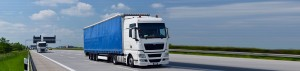 blue hgv lorry driving on motorway