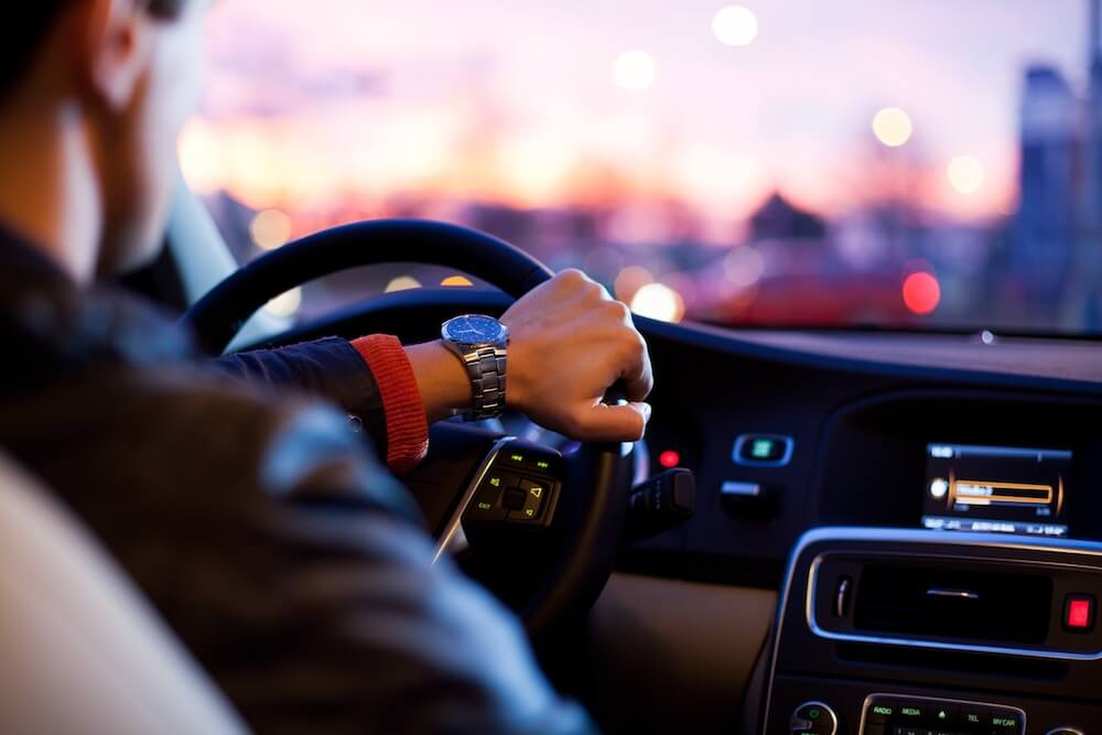 mans hand on the wheel and driving image