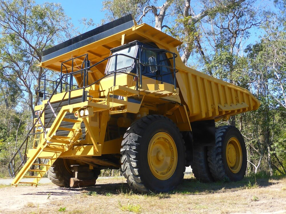large yellow truck in woods